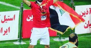 لاعب المنتخب الوطني بشار رسن يتوشح بالعلم العراقي في ملاعب الايرانية